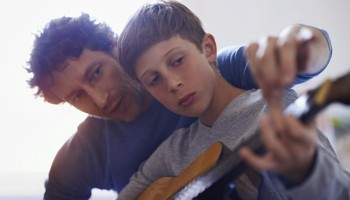 Shot of a boy learning to play guitar from his father
