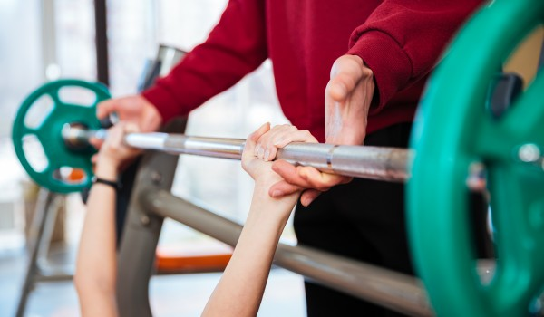 Hands of fitness instructor supporting to young woman athlete working out with barbell in gym